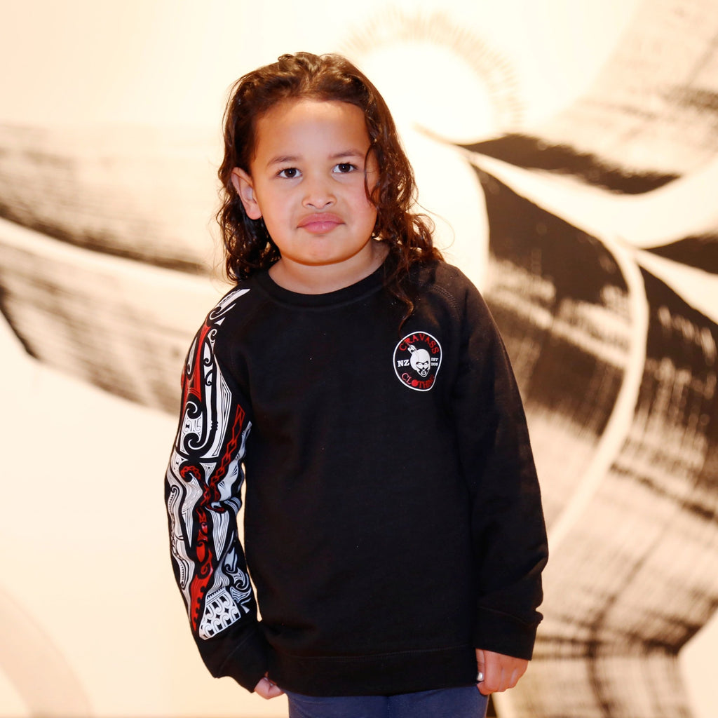 Cute maori girl wearing a black jersey with red and white maori designs on the sleeve. NZ Clothing