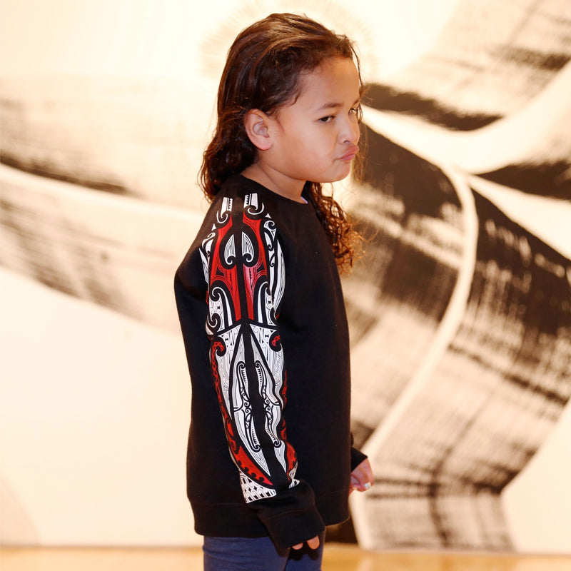 Side view of Cute maori girl wearing a black jersey with red and white maori designs on the sleeve. NZ Clothing