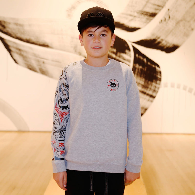 Boy wearing a grey crew neck jersey from cravass clothing with red and black maori sleeve.