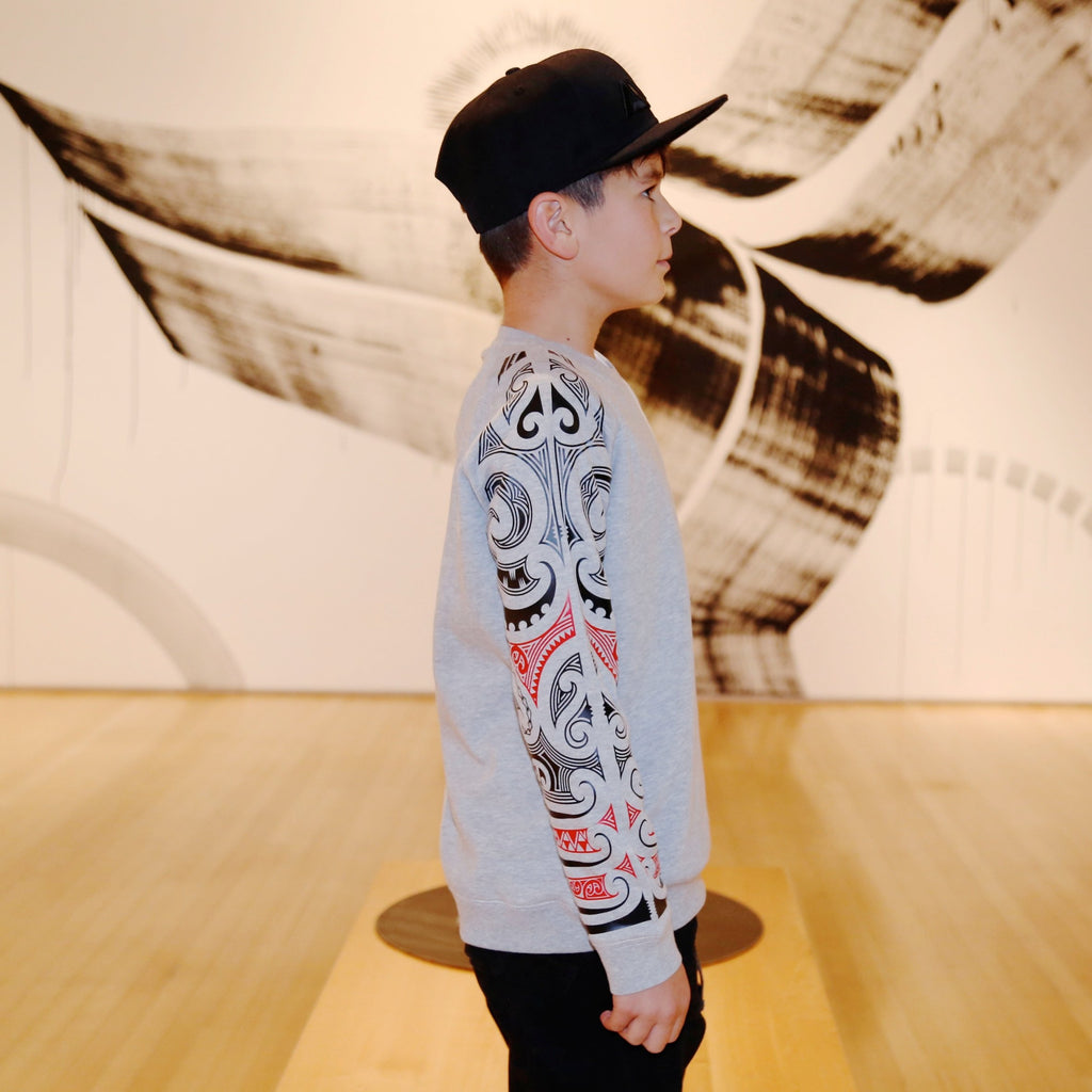 Side view of Boy wearing a grey crew neck jersey from cravass clothing with red and black maori sleeve.