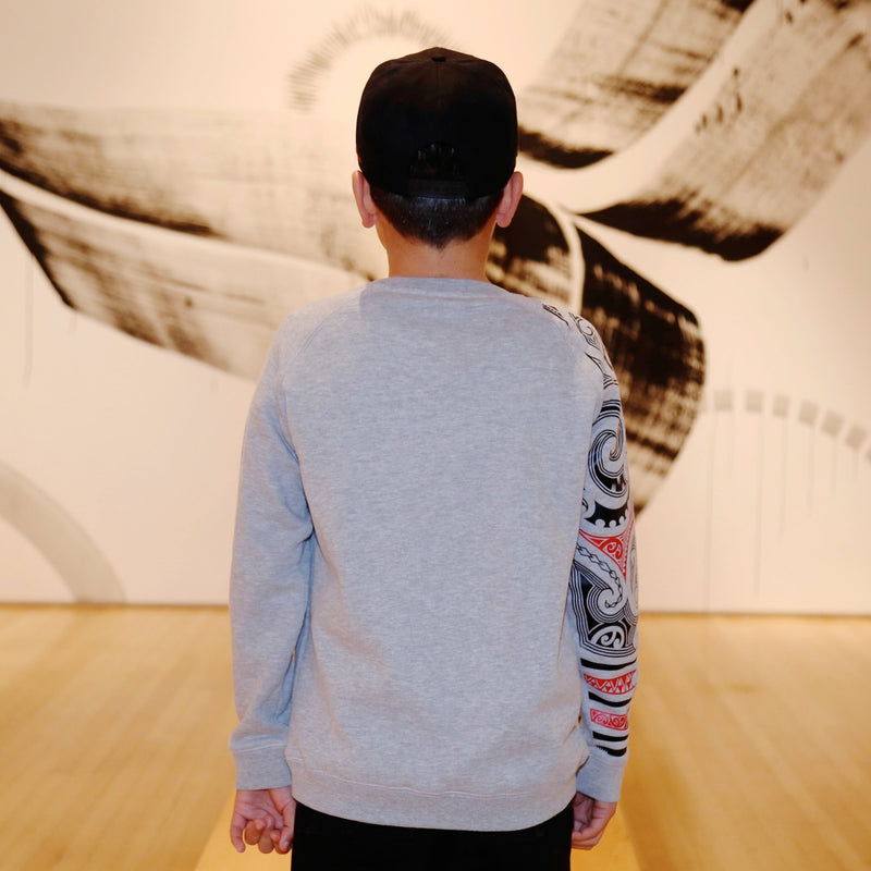 Back view of Boy wearing a grey crew neck jersey from cravass clothing with red and black maori sleeve.