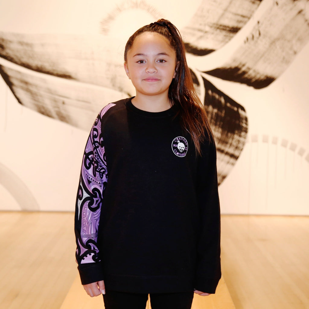 Cute maori girl wearing a black jersey with purple and white maori design on the sleeve.