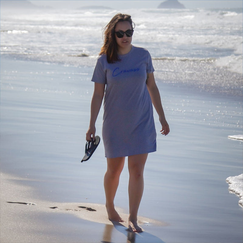 Beautiful wahine walking along the papamoa beach wearing a grey cravass tshirt dress.