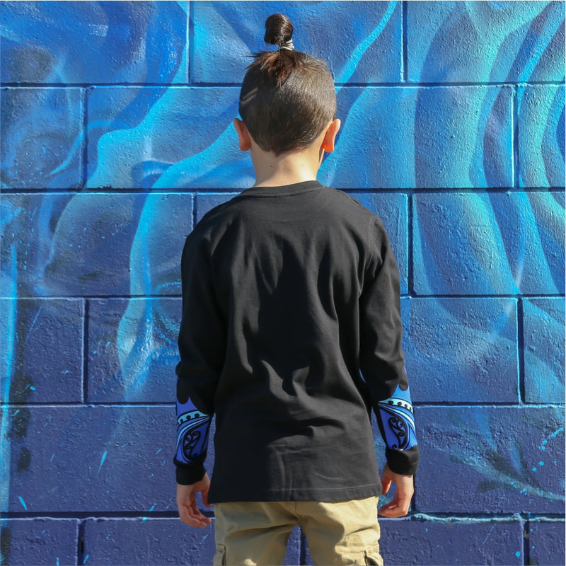 Young boy wearing black long sleeve tshirt with blue maori design on the forearm form cravass clothing. Back