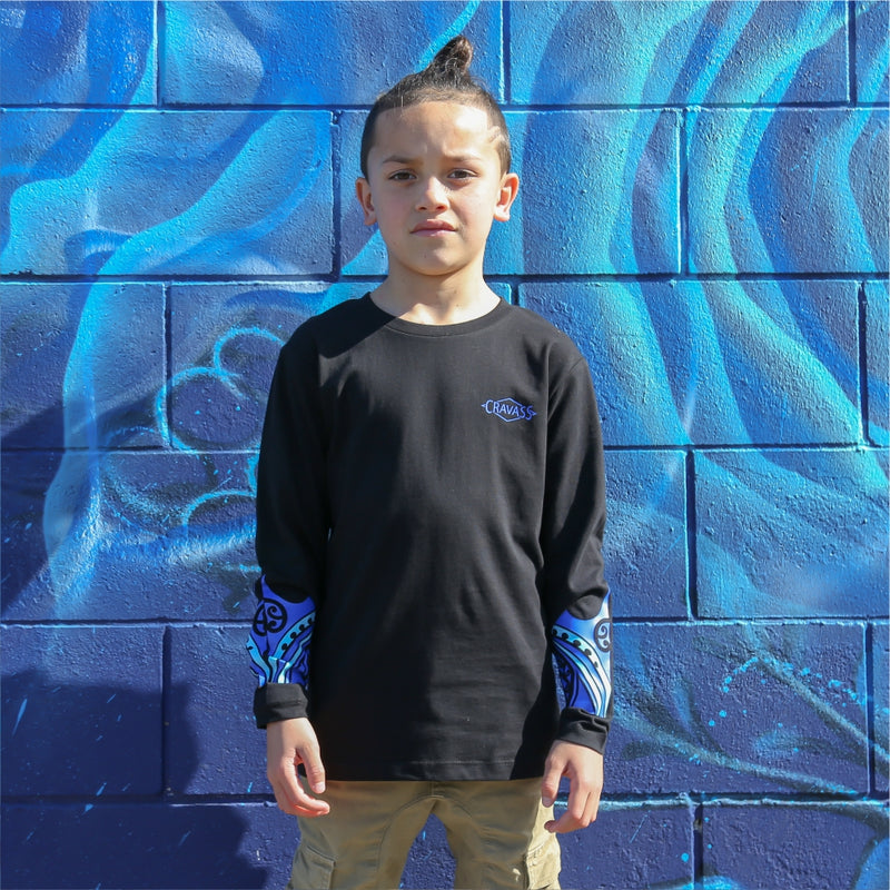 Young boy wearing black long sleeve tshirt with blue maori design on the forearm form cravass clothing. front