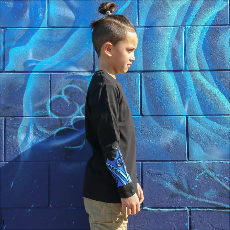 Young boy wearing black long sleeve tshirt with blue maori design on the forearm form cravass clothing. Side