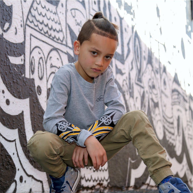 Young boy wearing cravass clothing with maori design with street art in the background.