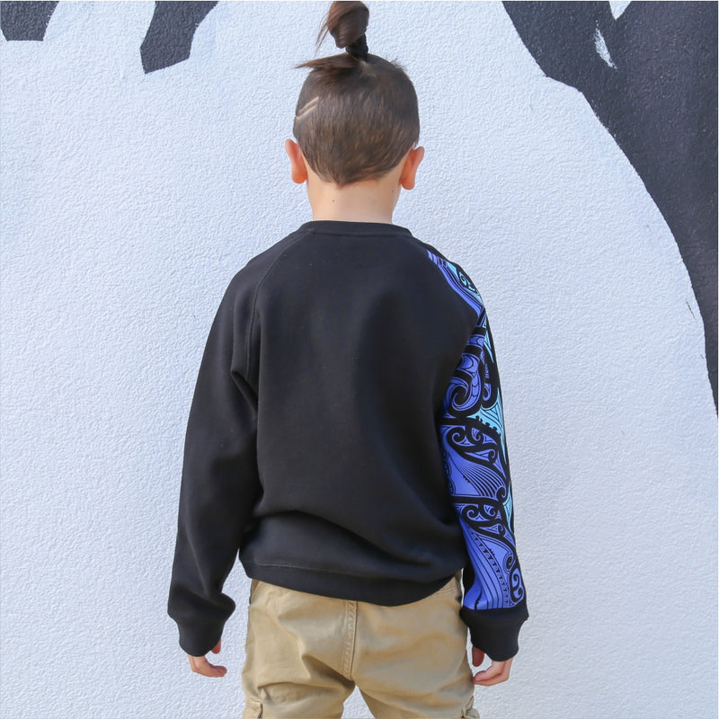 Childrens black jersey with blue maori design on the sleeve. Back