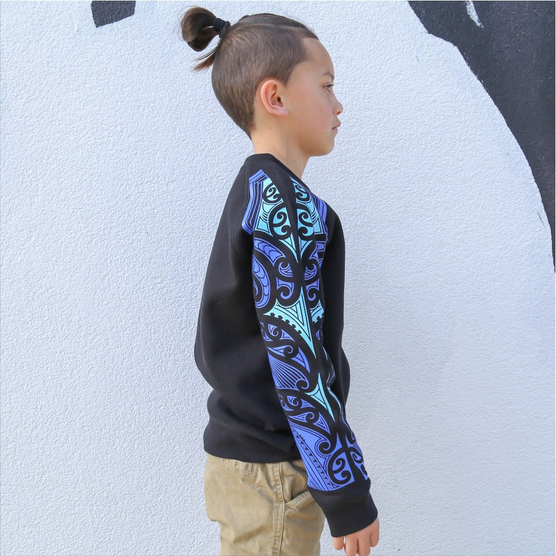 Childrens black jersey with blue maori design on the sleeve. Side