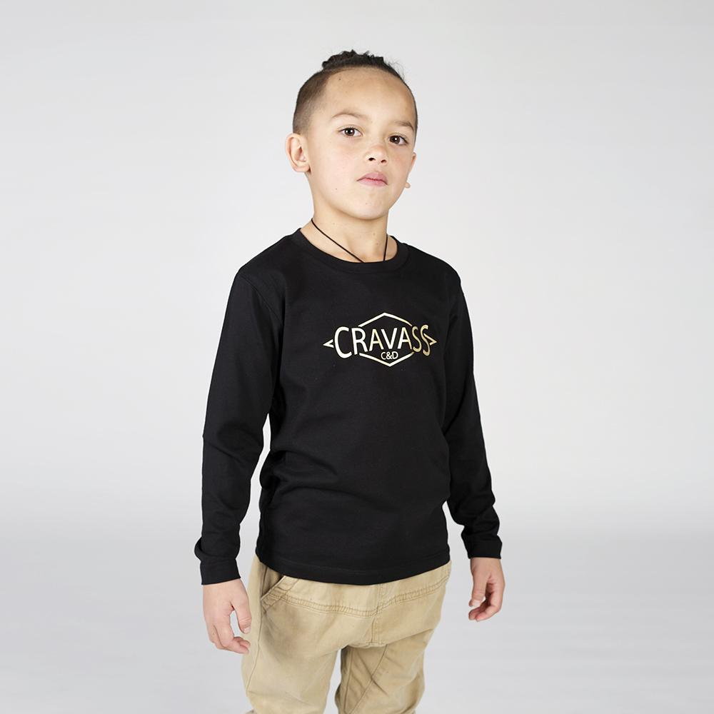 Boy wearing a black long sleeve tshirt with gold cravass clothing logo on the front.