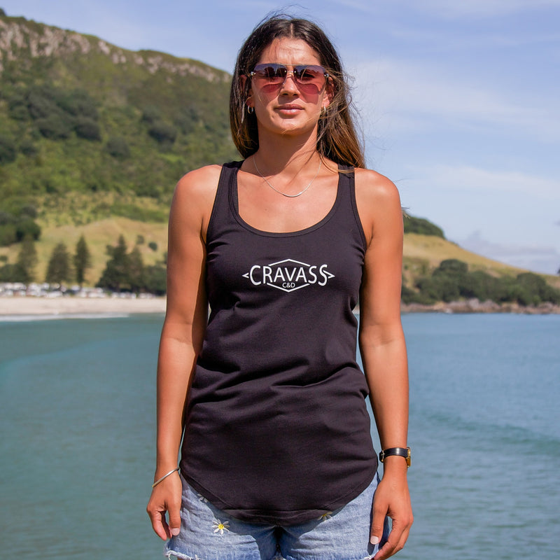 Model wearing a womens black singlet with a white and green ta moko design down the back. At Mt Maunganui beach. Front view.