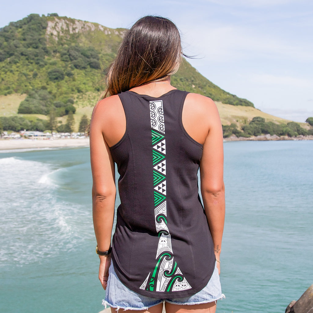 Model wearing a womens black singlet with a white and green ta moko design down the back. At Mt Maunganui beach. Back view.