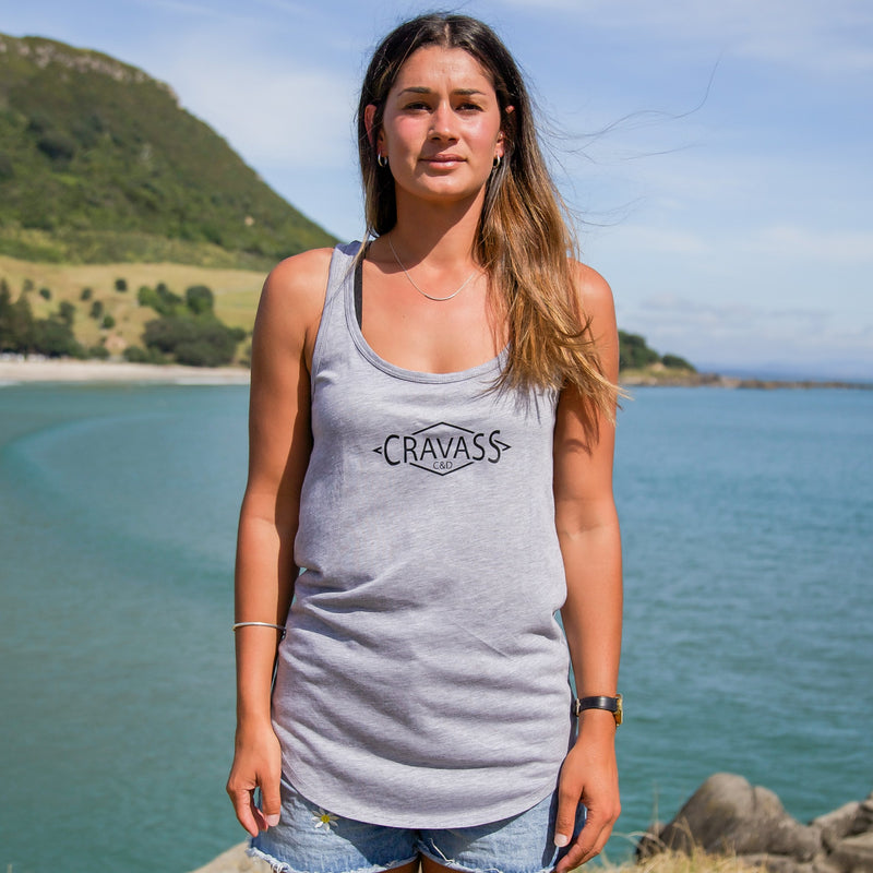 Model wearing a womens grey singlet with a black and green maori ta moko design down the back. At Mt Maunganui beach. Front view.