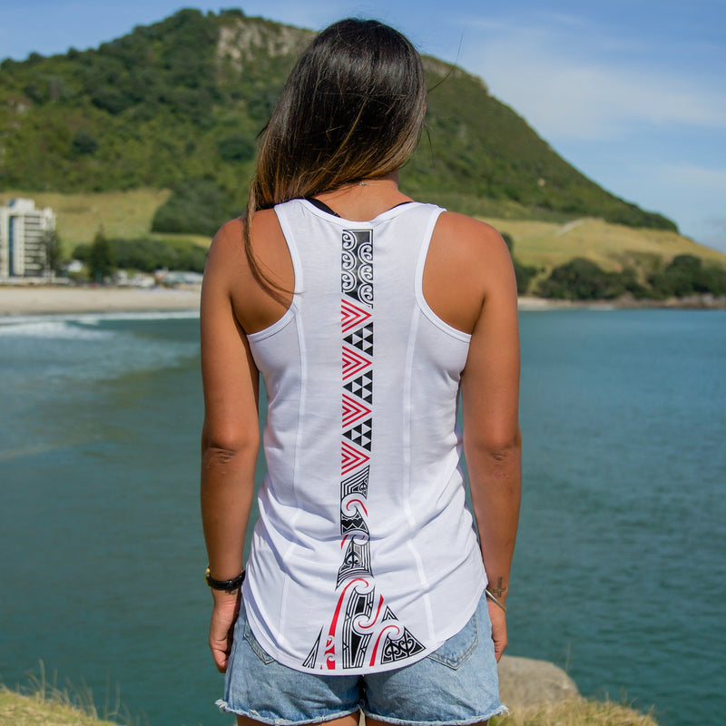 Model wearing a womens white singlet with a red and black Maori ta moko design down the back. Mt Maunganui in the background