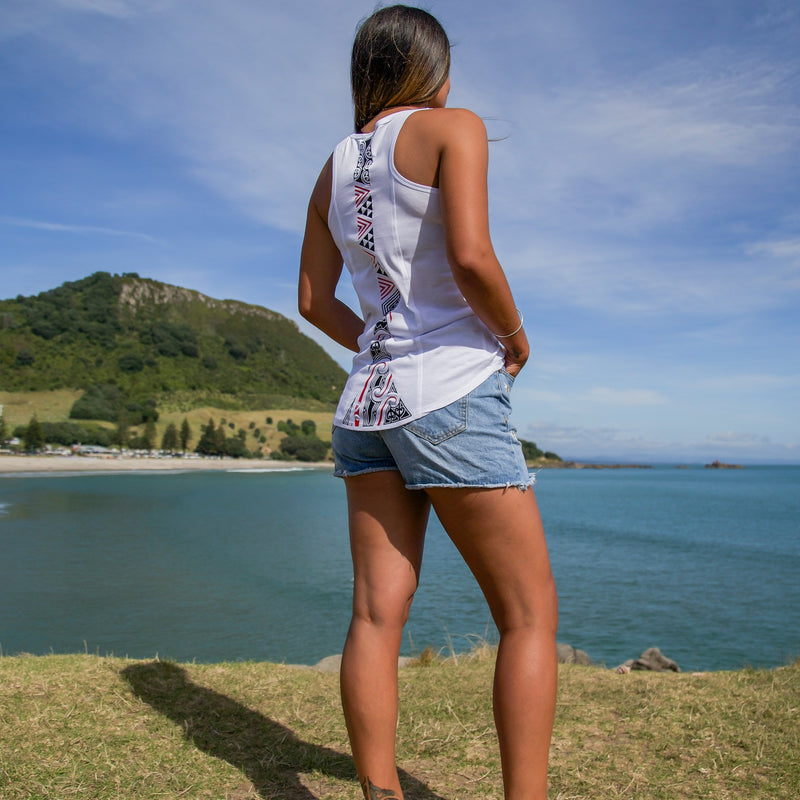 Model wearing a womens white singlet with a red and black ta moko design down the back. Mt Maunganui in the background