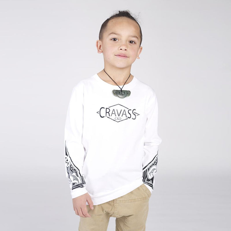 Young boy wearing white cravass long sleeve tshirt with black maori ta moko design on both forearms.