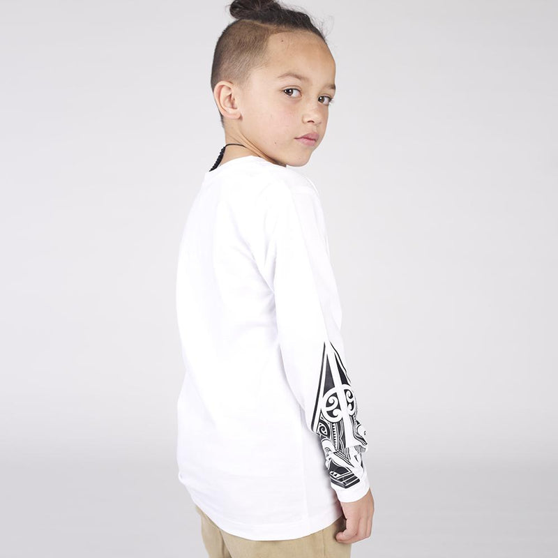 Side view of young boy wearing white cravass long sleeve tshirt with black maori ta moko design on both forearms.