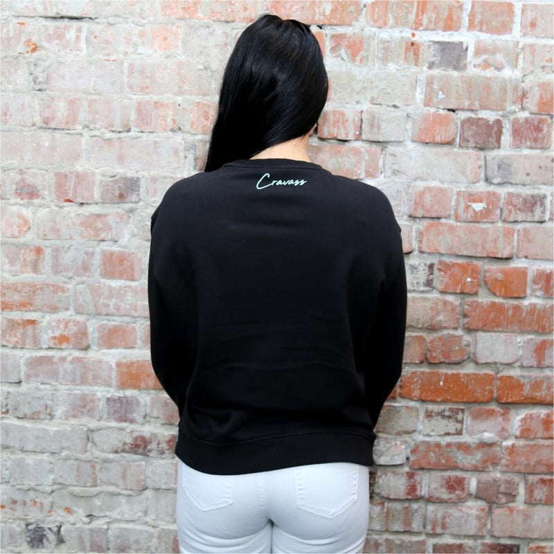 Model wearing a women's black jersey with maori ta moko designs on the forearms. Back view.