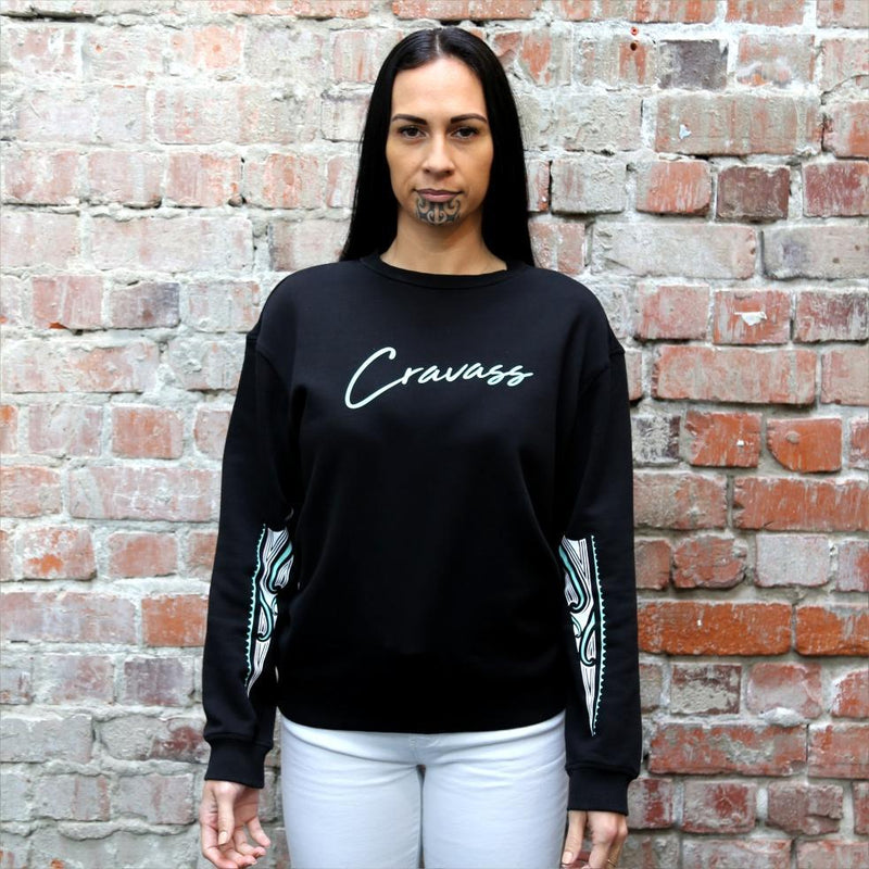 Model wearing a women's black jersey with maori ta moko designs on the forearms.
