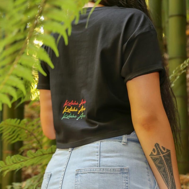 Women's black crop top with Rasta coloured Maori design from Cravass Clothing. Back