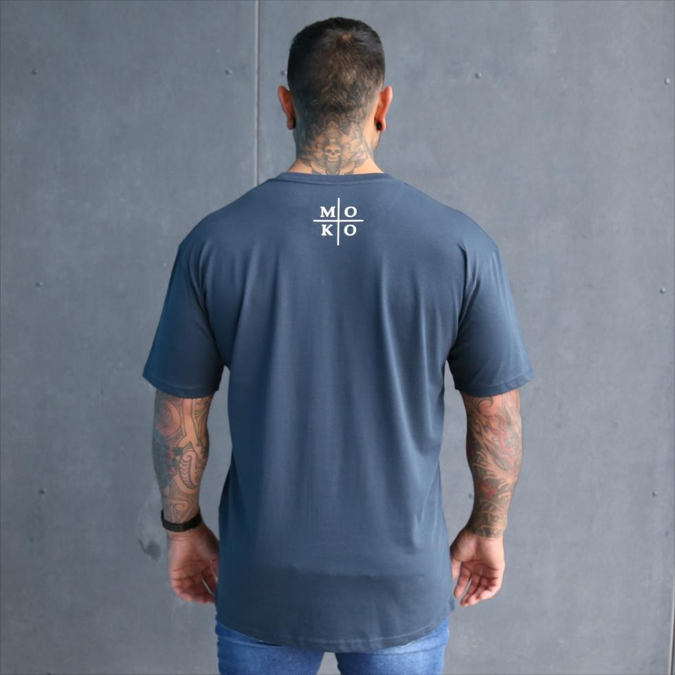 Mens blue tshirt with white maori wording design. Moko - maori artform or tattoo. Back view