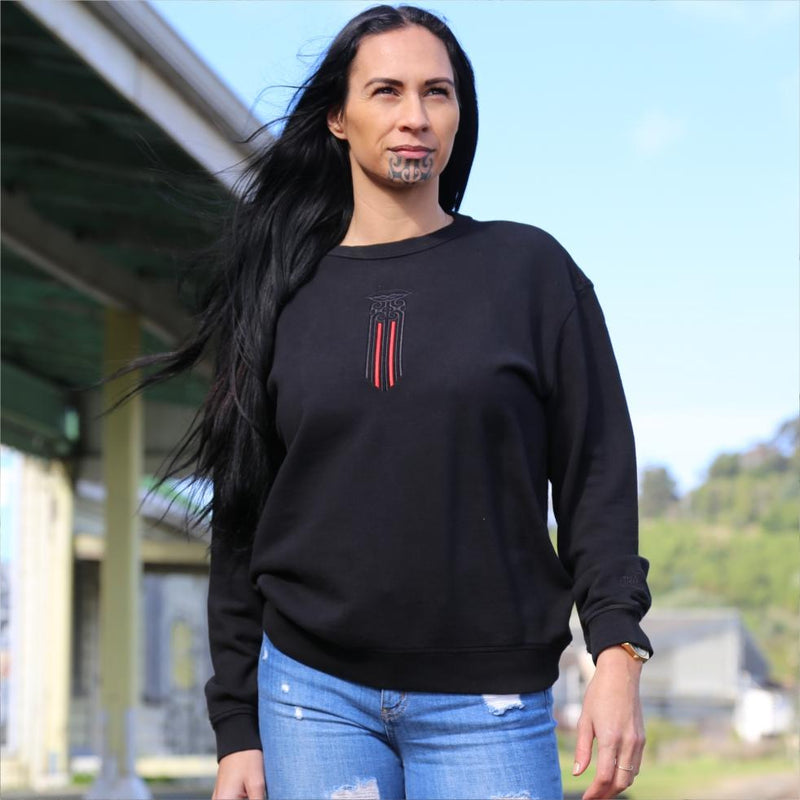 Women's black crew jersey with a black and red Maori moko kauae design. outside gisborne railway station nz