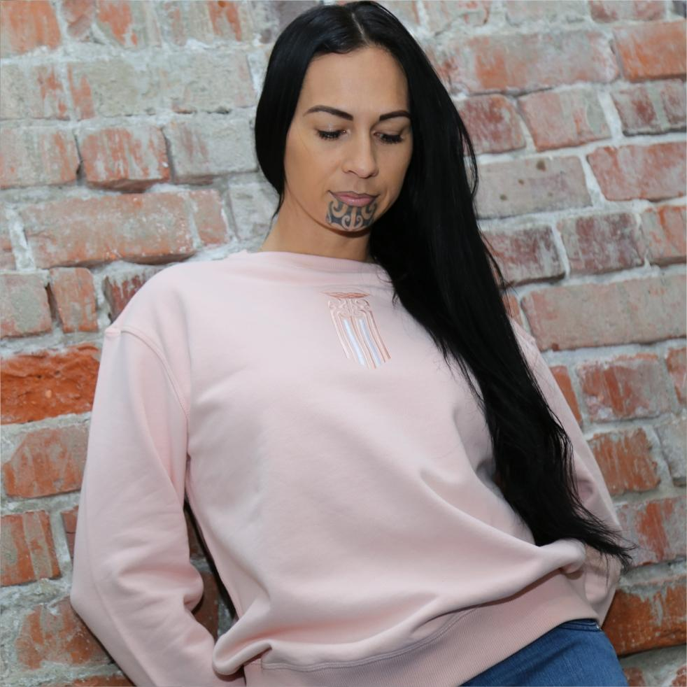 Model wearing pink jersey with a moko kauae embroidered maori design