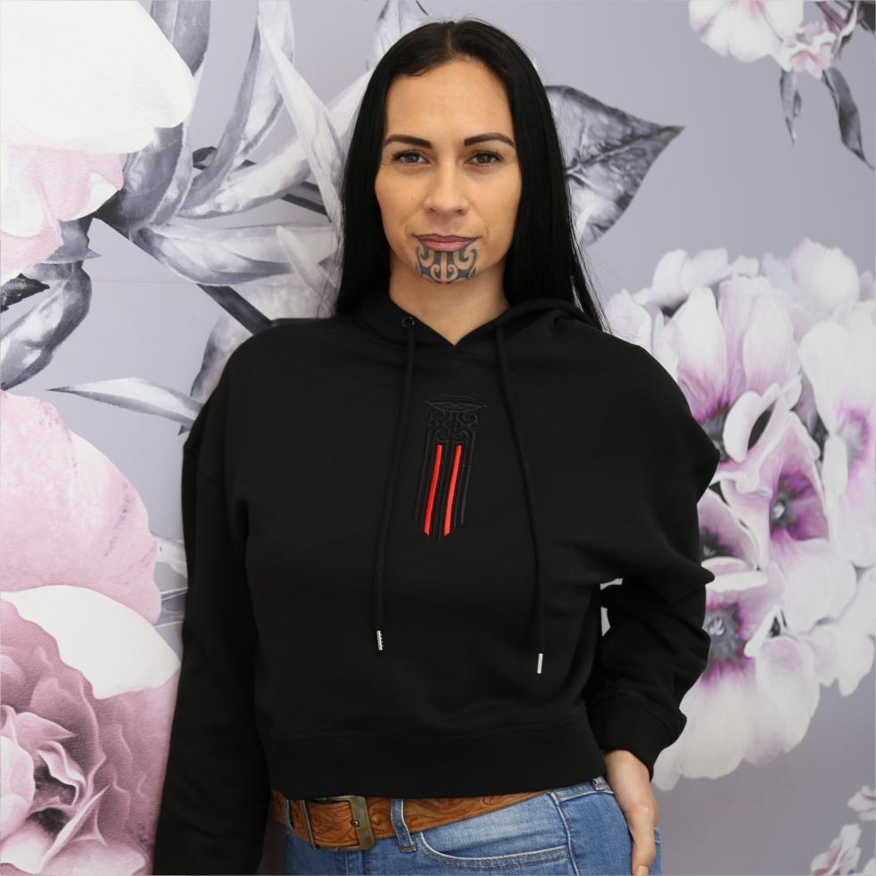Black women's crop hoodie with black and red maori moko kauae design.