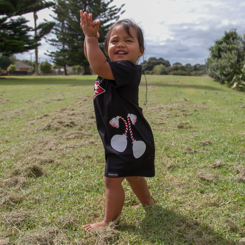 Girls black t shirt dress with red and white maori poi design.