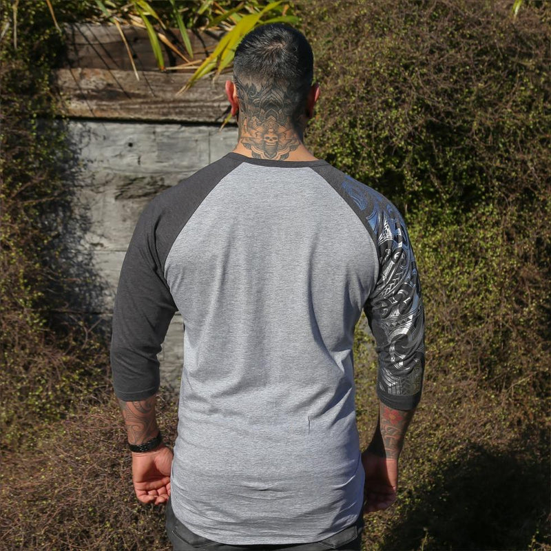 Male model wearing two tone grey raglan tshirt with silver ta moko sleeve. Back view.