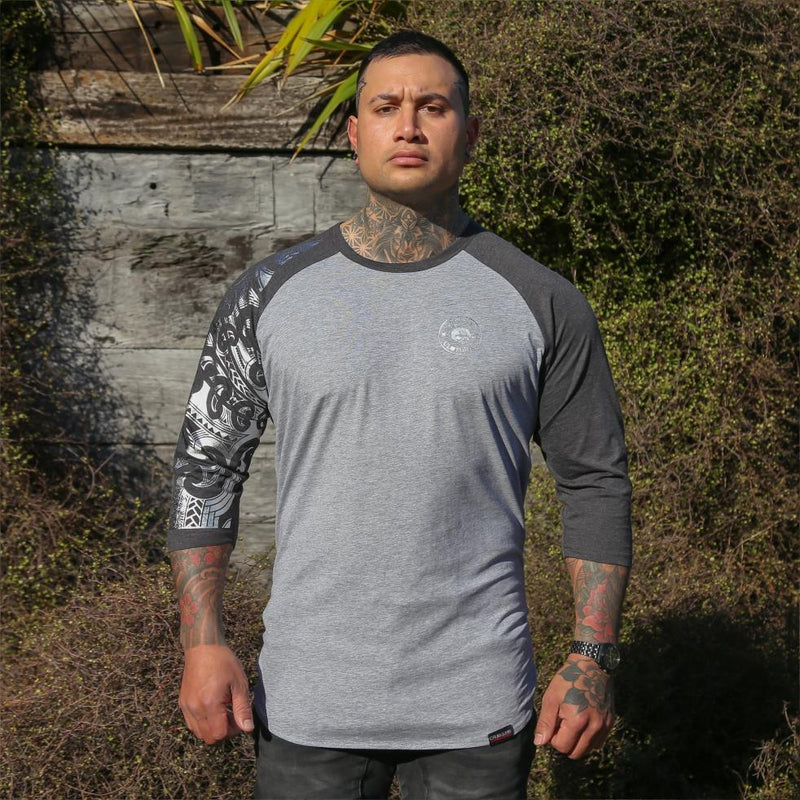 Male model wearing two tone grey raglan tshirt with silver ta moko sleeve. front view.