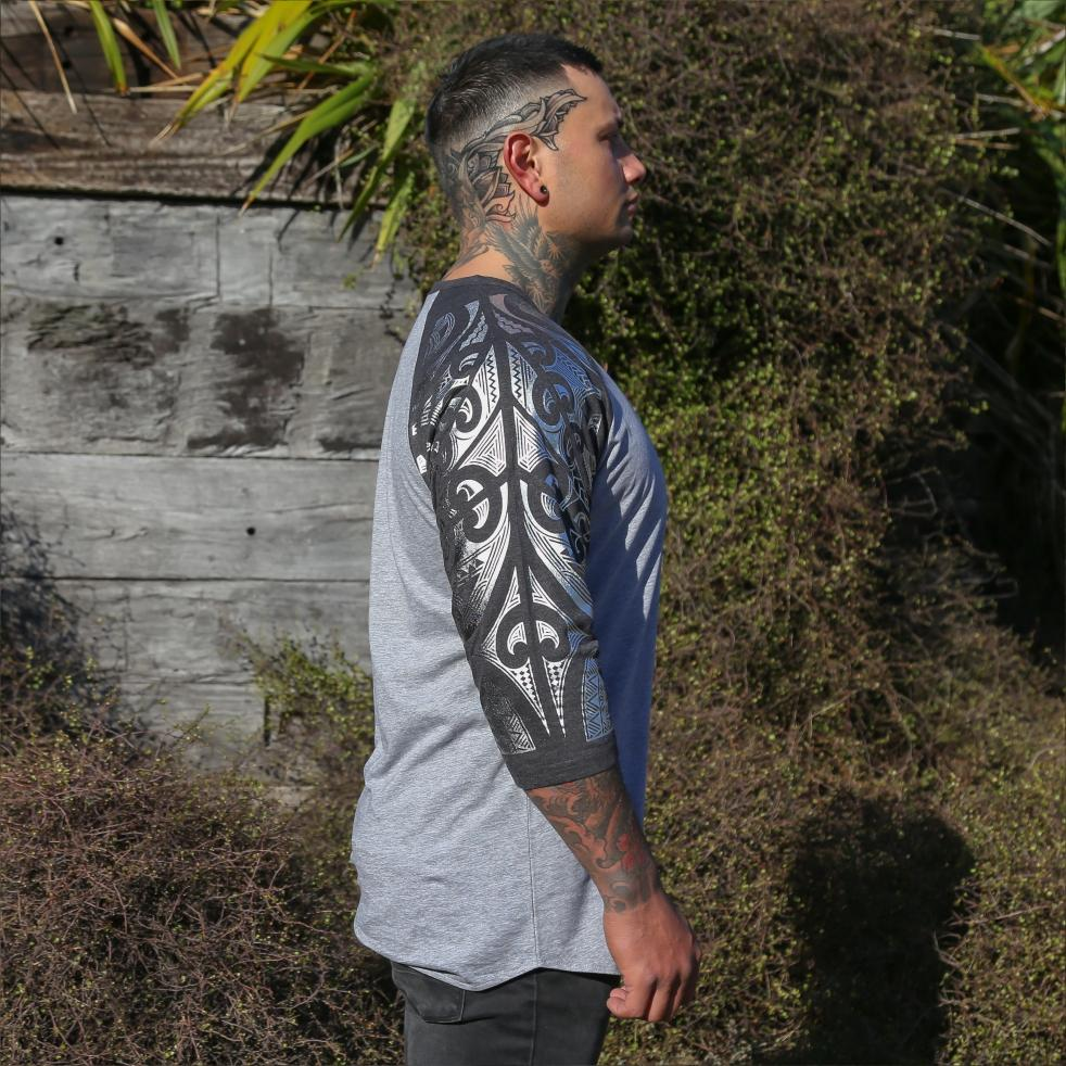 Male model wearing two tone grey raglan tshirt with silver ta moko sleeve. Side view.