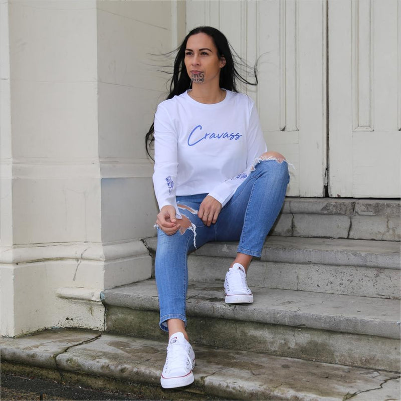 Model sitting on stairs wearing a white long sleeve tshirt with maori design.