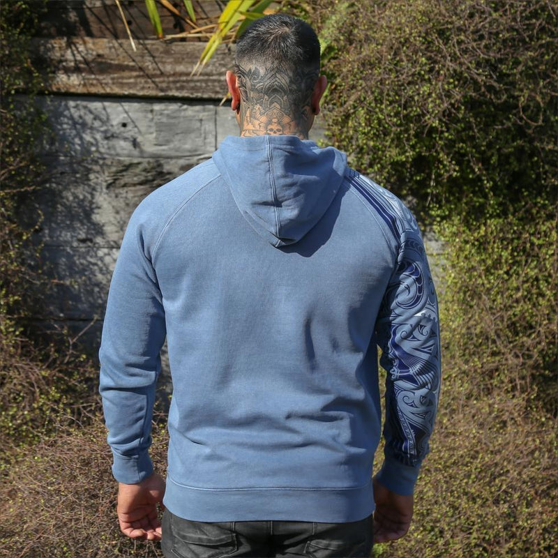 Blue unisex hoodie with blue and white ta moko new zealand maori sleeve design. Back view