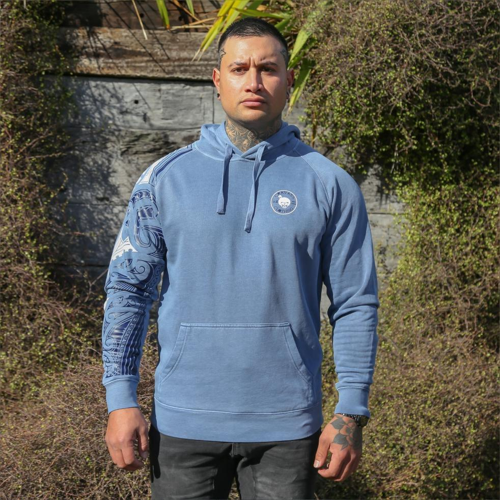 Blue unisex hoodie with blue and white ta moko new zealand maori sleeve design. Front view