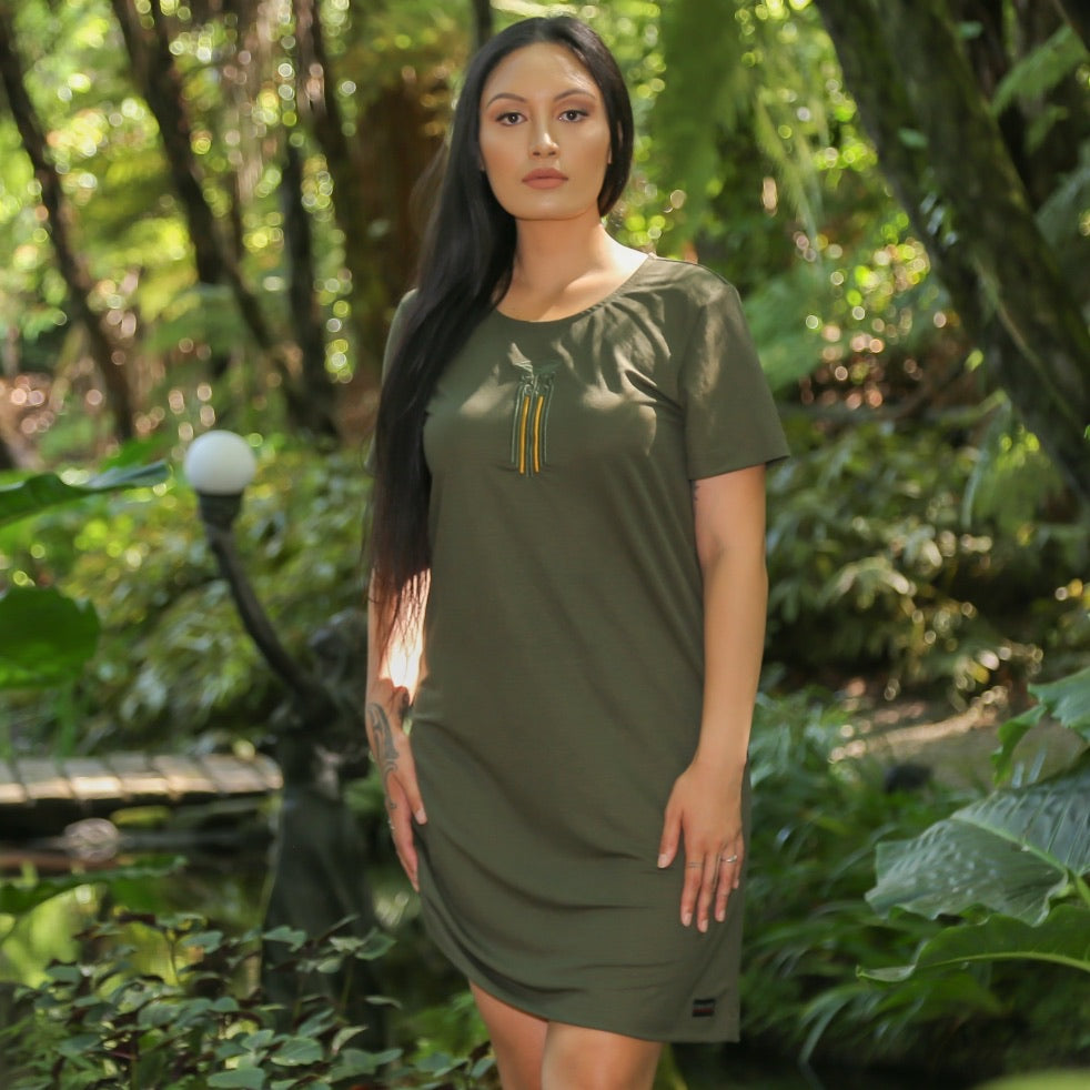 Women's green dress with stunning embrodered Moko Kauae design in matching green and contrasting mustard.