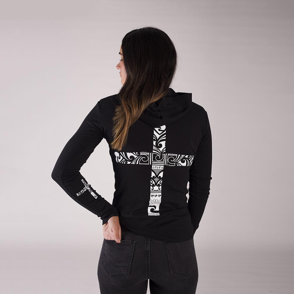 Beautiful female model wearing a black Cravass light hood with a maori inspired cross design on the back.