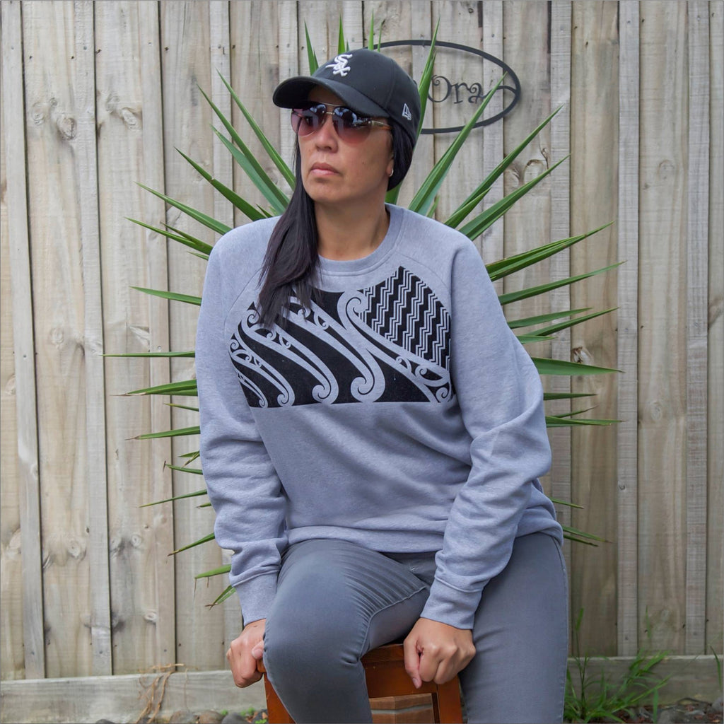 Beautiful model wearing a unsex grey jersey with textured maori design on the front chest