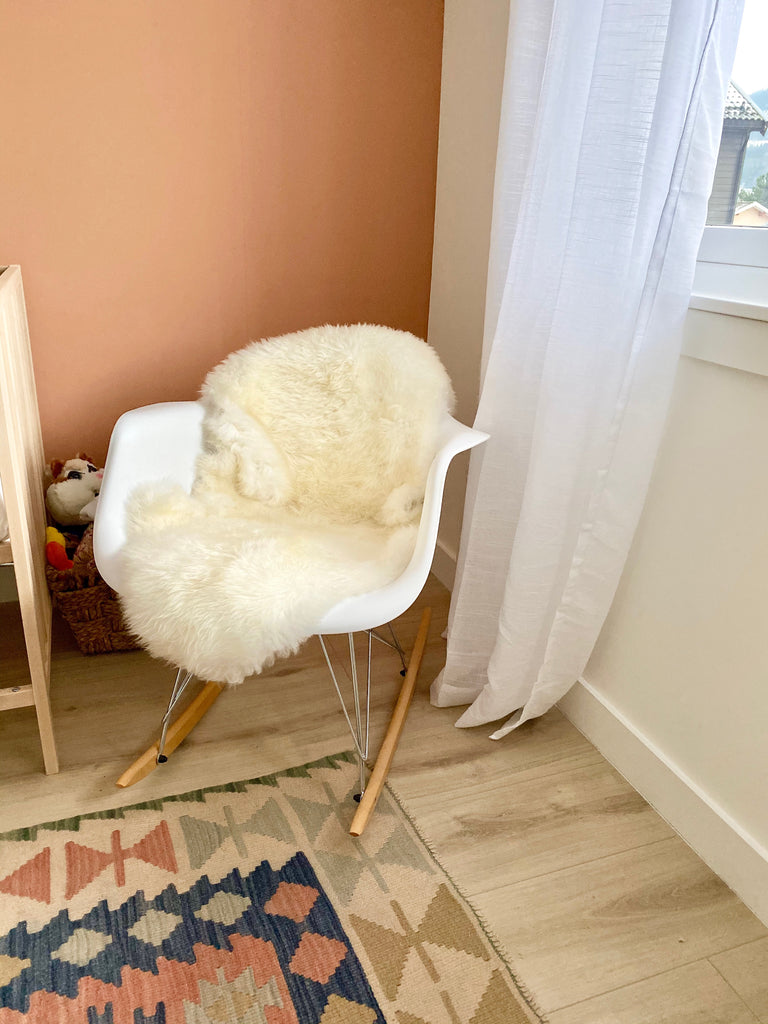 Scandinavian Nursery - white Ikea rocking chair covered with a cozy throw