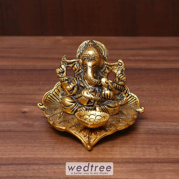 White Metal Ganesha In Pipal Leaf With Diya Gold Finish - W3630 Diyas & Candle Holders