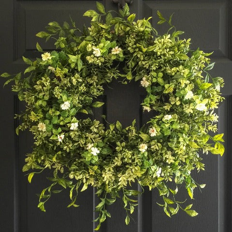boxwood wreath with white tea leaf flowers