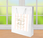 White gloss bag with broad blush stripes and gold text