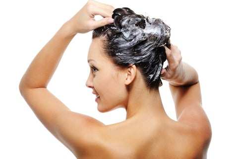 Image of a young brunette woman shampooing her hair