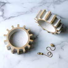 sculptural gear or cog tray on marble table