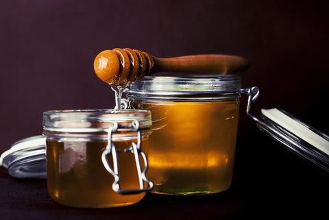 Two glass jars with airtight lids full of honey and a wooden honey dipper.