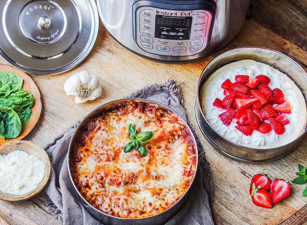 Multiple ecozoi pots near an Instant Pot, with one pot containing a baked lasagna and the other a strawberry cheesecake.