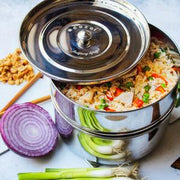 Stacked cooking inserts surrounded by vegetables and filled with vegetable fried rice.