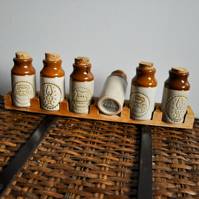 Six Small Brown Jars With Cork Lids And Wooden Rack