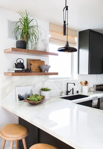 White kitchen with white counter tops, black cabinets, floating solid oak shelves and wooden stools. Interior design blog about our tips on bringing your kitchen to life without spending too much money. Written by vintage-etc in Cape Town. We make custom made & bespoke tables, benches, free-standing kitchen islands, desks, media units & wardrobes in our Cape Town & Johannesburg workshops – using Oak, Oregon, Ash, Beech, Birch Ply & Meranti. We also sell imported furniture, provide design consulting services & make soft furnishings e.g. sofas & upholstered chairs in linen, velvet & stain resistant fabric.
