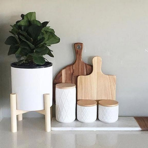 White kitchen with green Fiddle Leaf Fig Plant in a white vase next to a white cutting board with 3 white containers and 2 wooden cutting/chopping boards. Interior design blog about our tips on bringing your kitchen to life without spending too much money. Written by vintage-etc in Cape Town. We make custom made & bespoke tables, benches, free-standing kitchen islands, desks, media units & wardrobes in our Cape Town & Johannesburg workshops – using Oak, Oregon, Ash, Beech, Birch Ply & Meranti. We also sell imported furniture, provide design consulting services & make soft furnishings e.g. sofas & upholstered chairs in linen, velvet & stain resistant fabric.
